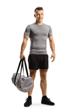 Young man holding a sports bag and smiling at the camera