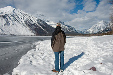 Man looking at snow covered mountains