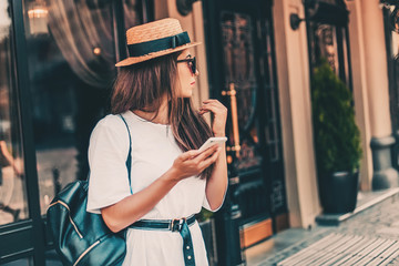 Young stylish woman using phone walking on the street, travel with backpack, straw hat, wearing trendy outfit. Wall mural