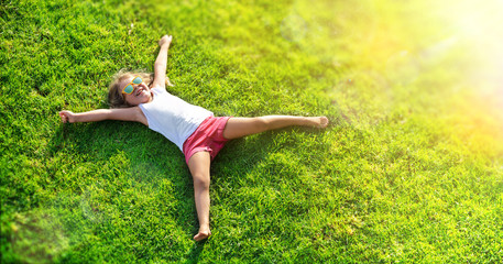 Smiling Little Girl Lying On Grass Meadow