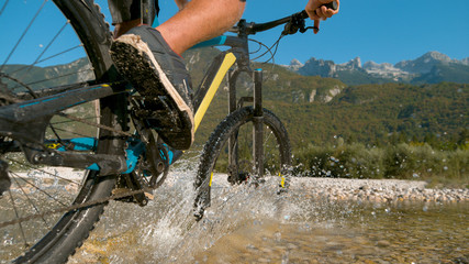 CLOSE UP: Active man splashes water while riding an electric mountain bike.