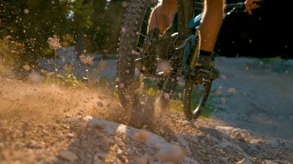 CLOSE UP, DOF: Mountain biker kicking up dust and rocks while braking hard