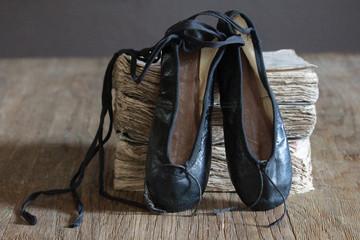 vintage black ballet shoes and old books