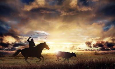 rancher lassoing a runaway cow