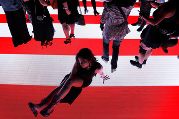 """Attendees walk on the illuminated runway following Alexander Wang's """"AW Collection 1"""" presentation at the Rockefeller Center in New York"""