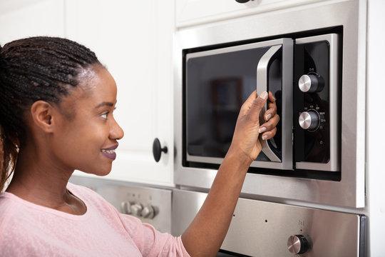 African Women Hand Opening The Oven Door