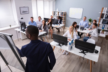 Colleagues Looking At Male Manager Giving Presentation In Office