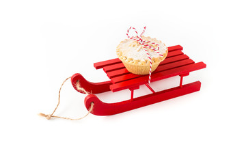 Red Wooden Sledge with Mince Pie Isolated on White