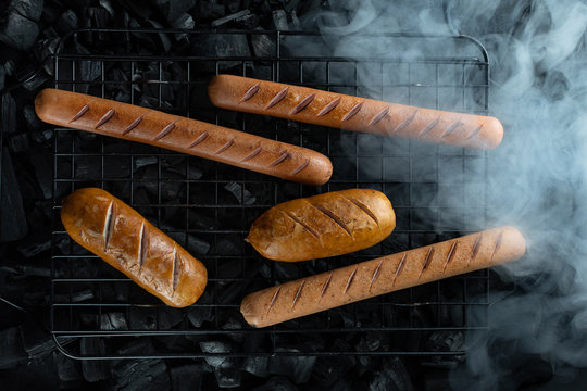 sausages on a grill with smoke of different shapes, barbecue. dark background, barbecue grill and charcoal. menu background, barbecue recipe, German cuisine, pork beef, hot dog