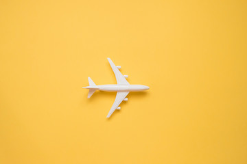 Flat lay design of travel concept with plane on yellow background with copy space. Wall mural