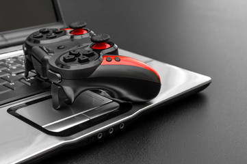 Gamepad with laptop on black background.