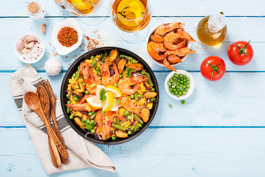 Traditional spanish seafood paella in the fry pan on a blue wooden  table, top view.