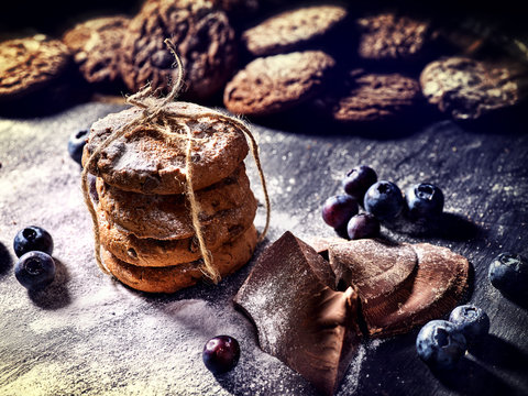Bakers gonna bake. Serving food on slate. Oatmeal cookies biscuit with blueberry on dark tiles countrylike. Chocolate chip cookies tied with string shop on window display. Homemade, delicious recipes.