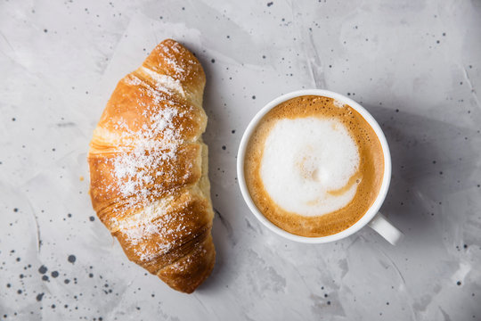 Beautiful and simple traditional French breakfast of fresh croissant and a cup of cappuccino