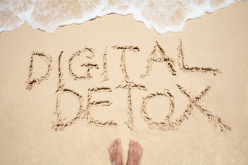 Person's Foot Near The Digital Detox Text Wave On Beach