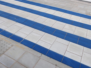 blue and white striped pedestrial crossing and a gray sidewalk
