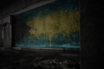 painted flag of bahamas on the dirty old wall in an abandoned ruined house.