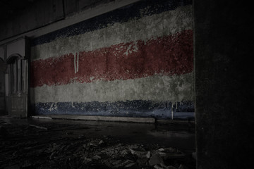 painted flag of costa rica on the dirty old wall in an abandoned ruined house.