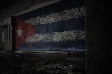 painted flag of cuba on the dirty old wall in an abandoned ruined house.