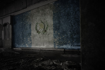 painted flag of guatemala on the dirty old wall in an abandoned ruined house.