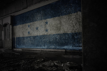 painted flag of honduras on the dirty old wall in an abandoned ruined house.