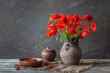 Still life in a rustic style: an old crock and a bouquet of red poppies and strawberry on a wooden table Fototapete