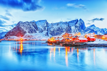 Amazing dusk panorama of picturesque peaks of Reine village on Lofoten Islands Archipelago in Norway. Classical red rorbu - traditional Lofoten fishing house and and street lights reflected in the sea