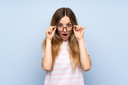 Young woman over isolated blue background with glasses and surprised