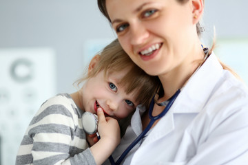 Paediatric doctor holding and hugging little cute girl patient