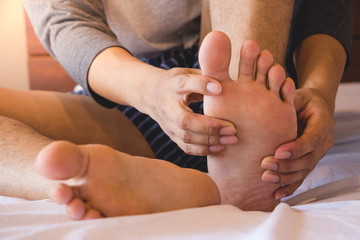 Foot Pain, young man sitting on the bed holding feel Having painful foot at home,Health concept.
