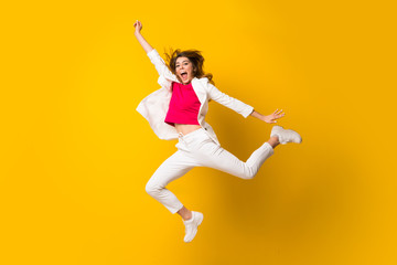 Young woman jumping over isolated yellow wall making victory gesture Wall mural