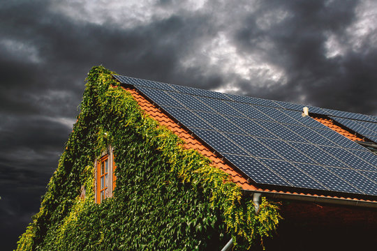 house roof with solar panels against a cloudy sky