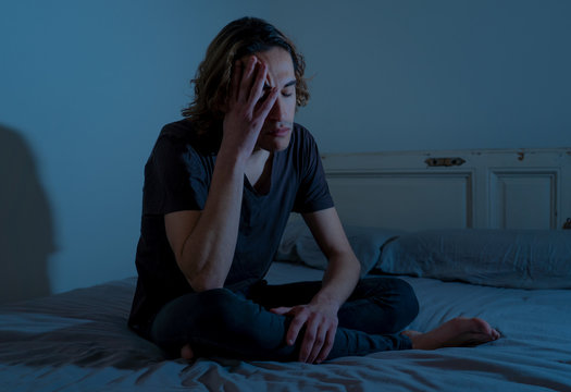 Desperate lonely teenager man suffering from depression sitting alone on bed