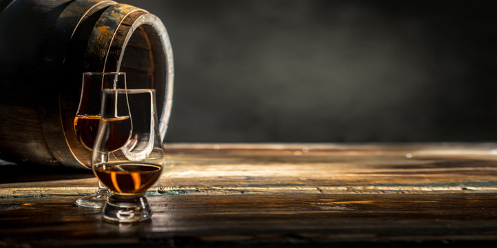 Two glasses of whiskey standing against an oak barrel