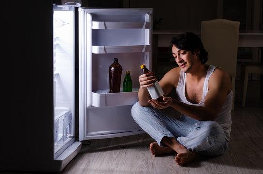 Man breaking diet at night near fridge