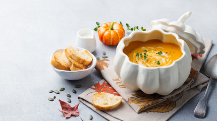 Pumpkin and carrot cream soup in bowl on grey stone background. Copy space.