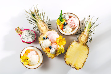 Balls of ice cream decoration flowers and berries in halves of coconut and  pineapple. Summer tropical concept.