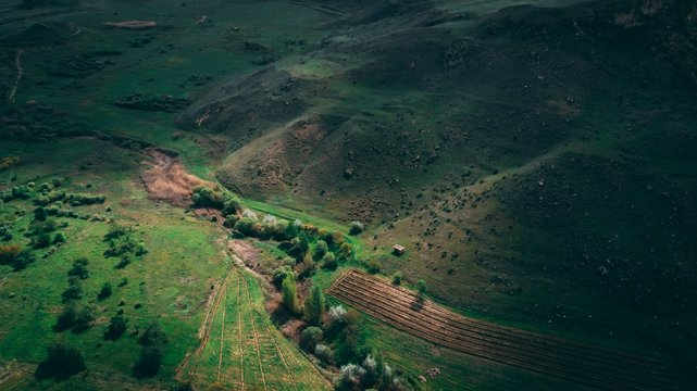 Aerial shot of beautiful green lands and hills of Armenia with amazing cloudy sky
