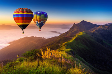 Wall Mural - Landscape of morning fog and mountains with hot air balloons at sunrise.
