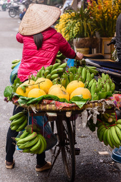 A woman carries fruit in baskets strapped to her bicycle in Hanoi, Vietnam