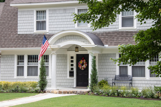 Neat and pretty shingled retro house with arched entryway and beautiful landscaping with colorful summer wreath on front door and American Flag attached to front column