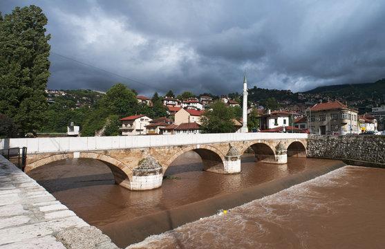 Sarajevo, Bosnia: skyline of the city seen from Seher-Cehajina cuprija, the stone pedestrian bridge which can be translated as Mayor's Bridge from Turkish work for mayor, crossing Miljacka river