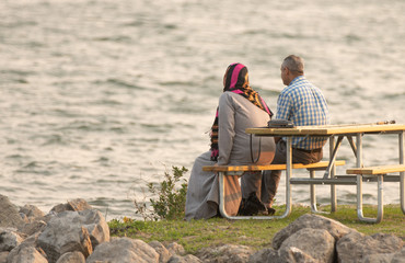 unknown middle eastern elderly couple sit at the park and enjoy the sunset