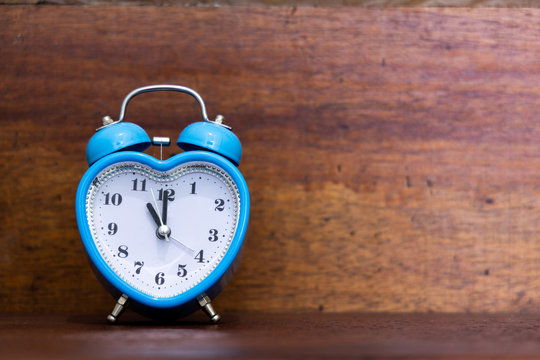 Heart shaped alarm clock on wooden background. Eleven O Clock