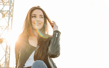 Beautiful charming brunette long hair happy asian girl in black leather jacket at sunset
