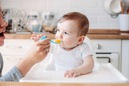 Charming little baby boy 6-8 months eating first food pumpkin from spoon with mom at home