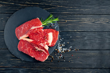Three pieces of juicy raw beef on a stone cutting board on a black wooden table background. Wall mural