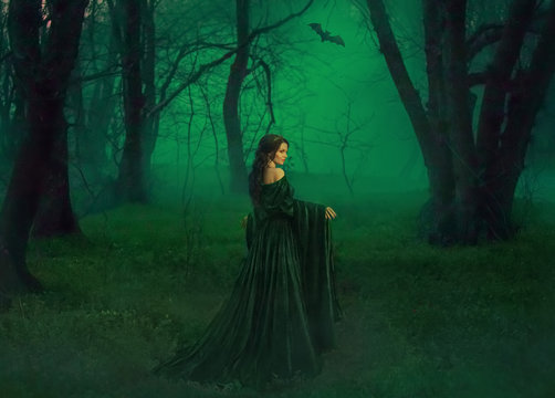 dark queen of otherworldly forces leads into realm of dead souls. bloody vampire in long velor emerald dress lures into her lair, lost pretty princess with dark hair lost her way and follows bat