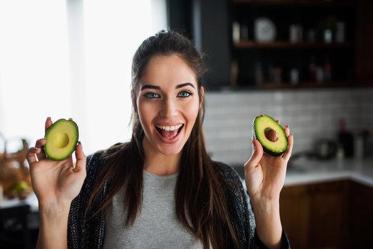 Beautiful smiling young woman preparing healthy food holding avocado
