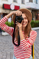 Glad tourist makes professional pics on camera, smiles broadly, focuses on beautiful landmark, strolls in center of city, wears hat, striped jumper, poses outdoor, enjoys nice summer journey